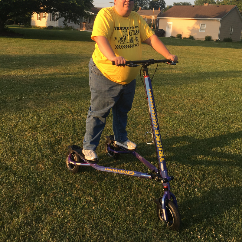 Rider wearing yellow t-shirt standing on blue Trikke T10 Roadster