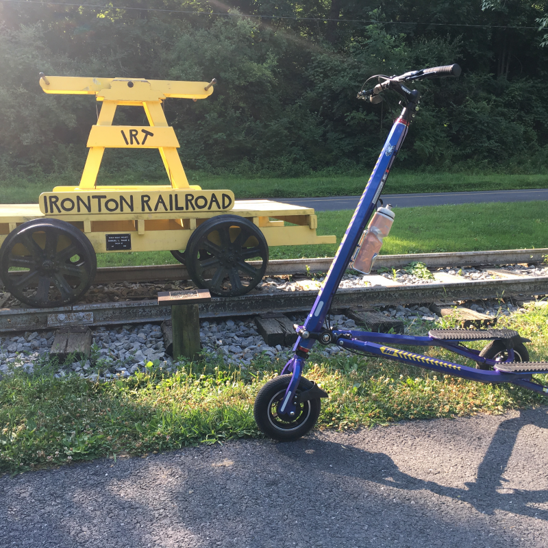 Blue Trikke T10 Roadster by old yellow Ironton Railroad pump car