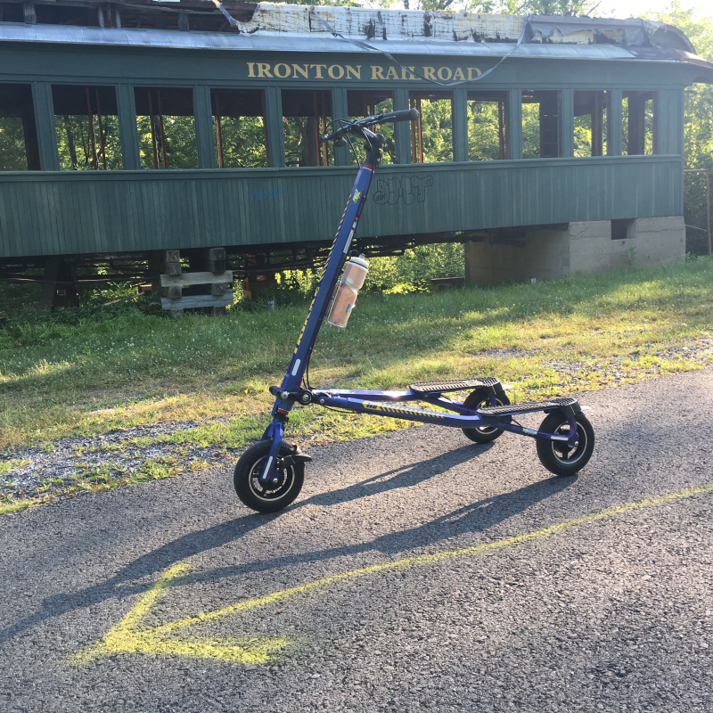 Blue Trikke T10 Roadster in front of dilapidated green Ironton Railroad passenger car