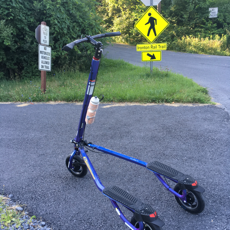 Blue Trikke T10 Roadster in front of Ironton Rail Trail sign