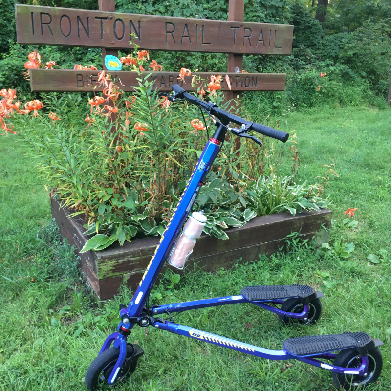 Blue Trikke T10 Roadster in front of Ironton Rail Trail sign and orange Lillies