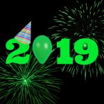 Green 2019 with party hat on the two and green fireworks against a black background